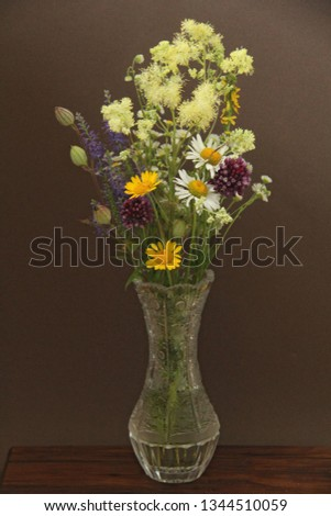 Summer wildflowers in a crystal vase. A beautiful summer bouquet on a dark background. Chamomile, wild onion, Veronica long-leaved. vertical, vertical design.