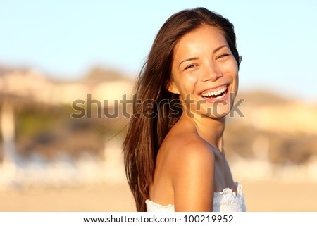 Summer woman portrait. Asian girl smiling happy laughing on beach vacation enjoying warm sunshine. Gorgeous mixed race Asian Chinese / Caucasian female model outside.