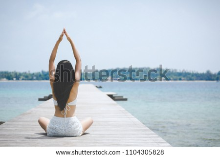 Summer woman vacations concept, Travel asia woman with white bikini meditation and practicing yoga on wooden bridge in sea at Koh Mak, Thailand