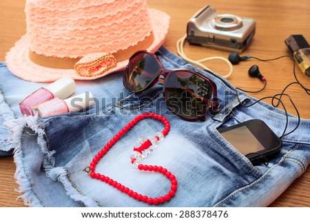 Summer women\'s accessories: red sunglasses, beads, denim shorts, mobile phone, headphones, a sun hat, camera, nail polish, perfum. Toned image