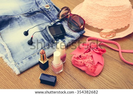 Summer women\'s accessories: sunglasses, beads, denim shorts, mobile phone, headphones, a sun hat, handbag, lipstick, nail polish. Toned image