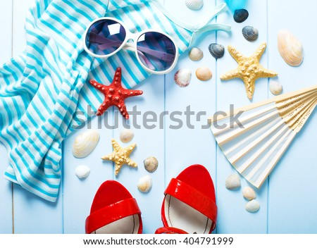 Summer women\'s accessories: sunglasses, red shoes, dress on blue wood background.