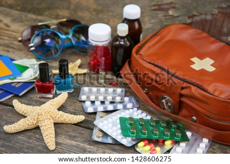 Summer women's beach accessories for your sea holiday and first aid kit on old wooden background. Concept of medication required in journey. Top view. Flat lay. #1428606275