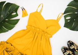 Summer women's fashion flat lay clothing and accessories: yellow dress, yellow earrings with a brush, colorful mules and palm leaves on a white background. Summer fashion shopping concept.
