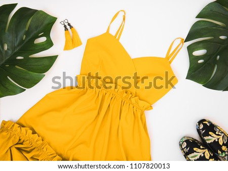 Summer women's fashion flat lay clothing and accessories: yellow dress, yellow earrings with a brush, colorful mules and palm leaves on a white background. Summer fashion shopping concept.  #1107820013