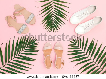 Summer women's shoes. Pink heeled sandal, silver glitter flat sandal, white lace up sneakers and tropical date palm leaves on pink background. Trendy beauty female background. Flat lay, top view. #1096111487