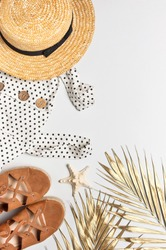 Summer women's white dress in black peas brown sandals straw hat golden palm leaf shells starfish on light background. Flat lay top view copy space. Women's beach fashion travel vacation golden shades