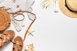 Summer women's white dress in black peas rattan woven bag brown sandals straw hat golden palm leaf shells starfish on light background. Flat lay top view. Women's beach fashion, travel vacation