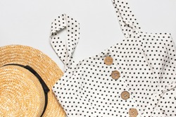 Summer women's white dress in black peas with natural wooden buttons and straw hat on light gray background. Flat lay top view. Women's fashion summer stylish sundress natural fabric. Beachwear