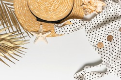Summer women's white dress in black peas with natural wooden buttons straw hat golden palm leaf shells starfish on light background. Flat lay top view copy space. Women's beach fashion travel vacation