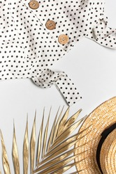 Summer women's white dress in black peas with natural wooden buttons straw hat golden palm leaf on light background. Flat lay top view copy space. Women's beach fashion, summer stylish sundress