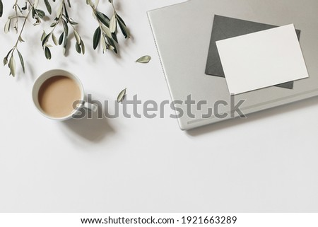 Summer working space composition. Blank greeting card, envelope mock-up scene. Cup of coffee, olive tree branches and laptop isolated on white table background. Flat lay, top view. Home office. Foto d'archivio ©