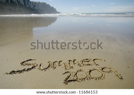 Summer 2009 written in the sand with ocean and sky background