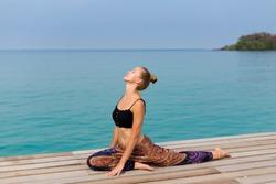 Summer yoga session on beautiful wooden pier, Bang Bao beach - tropical koh Kood island in Thailand. One-Legged King Pigeon Pose, Eka Pada Rajakapotasana