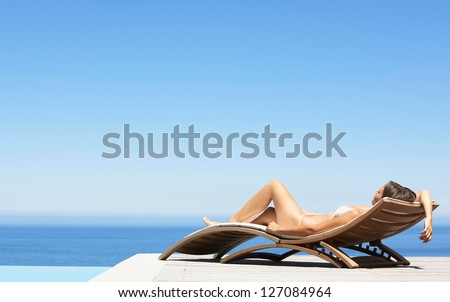 Summer young woman sunbathing in bikini on beach