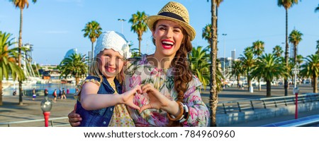 Summertime at colorful Barcelona. happy elegant mother and daughter tourists in Barcelona, Spain showing heart shaped hands #784960960