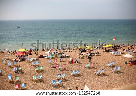 Summertime beach near ocean crowded with beach chairs and people on sunny day - stock photo