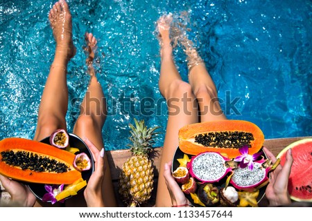 Summertime close up picture of two woman sitting near pool holding big plates with amazing sweet tasty tropical exotic fruits, papaya, mangosteen, dragon fruit watermelon and pineapple, healthy vegan. #1133457644