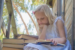 Summertime fun. Cute Blond Girl Reading Book Outside