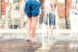 Summertime fun. Kids legs and feet wet in fountain. Outdoors.