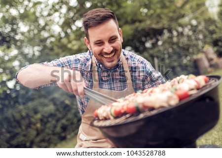 Summertime fun.Man cooking meat on barbecue for summer family dinner in the backyard of the house. #1043528788