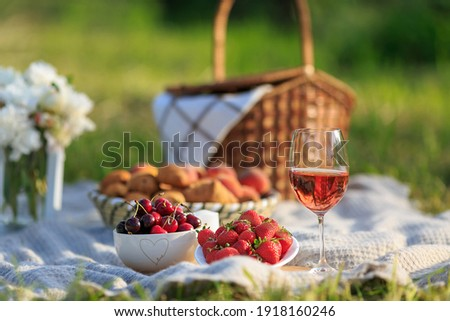 Summertime healthy picnic on nature background at sunny day. Close up Basket fruits strawberries, cherries, glass of red wine, on green grass in garden. Summer weekend outdoor. Beautiful still life Zdjęcia stock ©