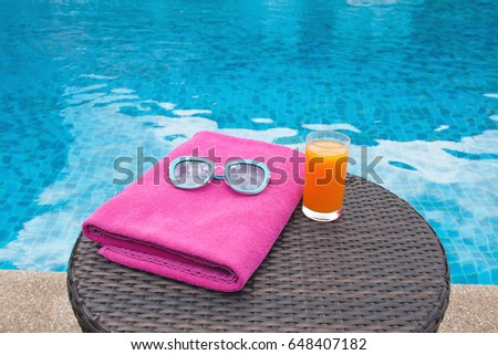 Summertime orange juice hat and sunglasses relax near swimming pool. #648407182