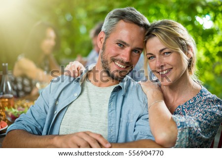 Summertime, portrait of a beautiful couple looking at the camera, they are sitting with friends around a terrace table to share a meal. Shot with flare