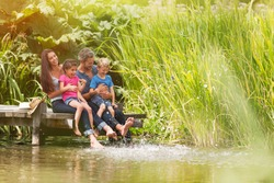 summertime, portrait of an happy family sitting on the edge of a wooden pontoon, feet in the river and making splashes