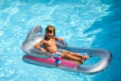 Summertime vacation. Child in pool. Boy swimming at swimmingpool. Funny kid on inflatable rubber mattress