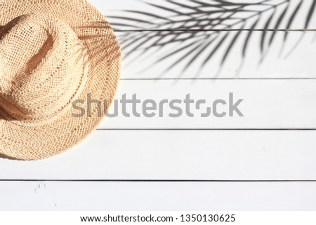 Summertime, vacation, travel, tourism concept. Summer straw hat and shadow of palm leaves on white wooden background. Summertime, vacation, travel, tourism concept. Top view, space for text.  #1350130625