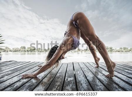 summertime yoga adult woman doing yoga in bikini on wooden river raft