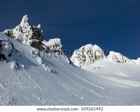 Summit of Mt. Hood in the State of Oregon, high mountain peaks with black rocks, jagged formations, snow covered hills and blue sky.
