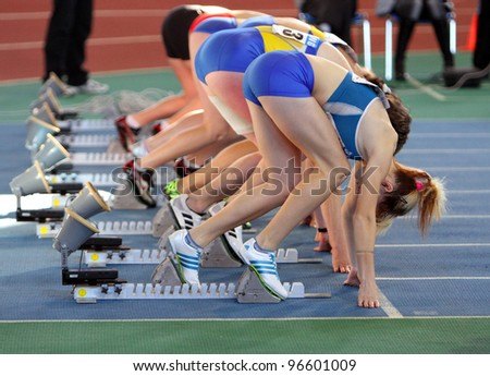 SUMY, UKRAINE - FEB.17: Unidentified girls on the start of the 60 meters dash during the Ukrainian Track and Field Championships on February 17, 2012 in Sumy, Ukraine.