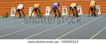 SUMY, UKRAINE -FEB.16: Unidentified men compete in the start of the 60 meters dash during the Ukrainian Track and Field Championships on February 16, 2012 in Sumy, Ukraine.