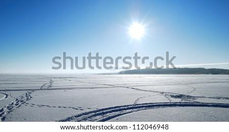sun above frozen lake in winter