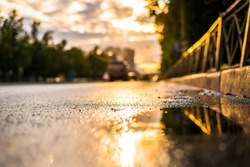 Sun after the rain in the city, view of the cars with a level of puddles on the pavement