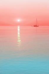 sun and a sailing boat in coral sunrise