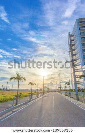 Sun and blue sky with asphalt road