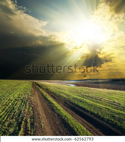 sun and clouds over road