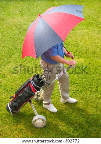 Sun and Rain a golfer caught in a spring shower.waiting for rain to pass.