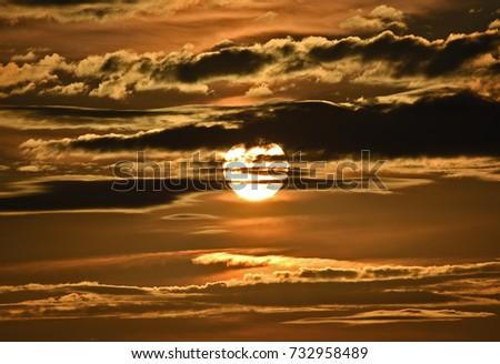Sun at sunset, behind cloud #732958489