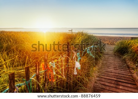 Sun at the horizon lights dunes and old-fashioned boardwalk on a Maine beach