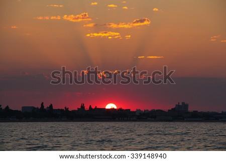 sun beam on sunrise over the city on sea