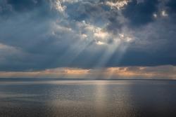Sun beam through heavy sky over calm Mediterranean sea. Sicily coast, Italy