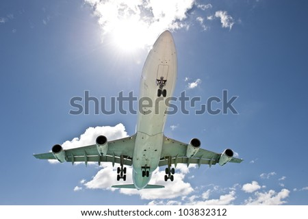 Sun beaming over a propelling airplane amidst a clear blue sky.