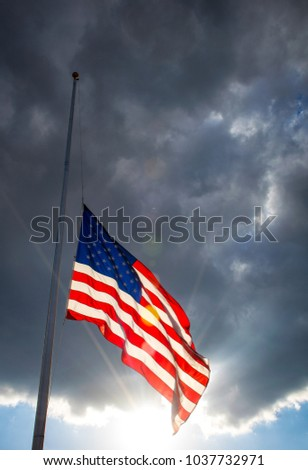 Sun beams and god beams illuminate the American Flag At Half Mast red, white , and blue Stars and Stripes lowered flag for memorial purposes
