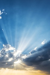 Sun beams breaking through the dark clouds at sunset. Hope, prayer, God's mercy and grace. Beautiful spectacular conceptual meditation background.
