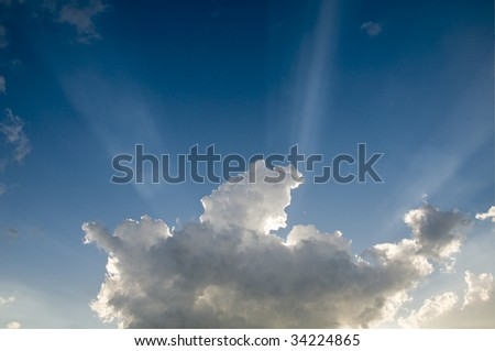 Sun beams bursting over a building storm cloud at sunset