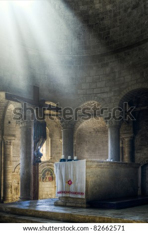 Sun beams illuminating Jesus Christ on the Cross and altar in old Monastery in Tuscany, Italy